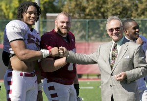 Sharif Finch, left, a junior at the Fox School of Business, bumps fists with Dr. M. Moshe Porat when the Fox School's Dean visited one of the Temple football team's October practices. Finch, a defensive lineman, is joined by senior Kyle Friend, the team's starting center and a fellow Fox student. (Ryan S. Brandenberg)