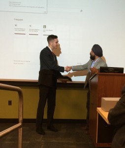 Fox School of Business student Robert Moses accepts the trophy for winning the Penn State Abington Business Challenge, shaking hands with Dr. Manohar Singh, division head for social sciences at Penn State Abington.