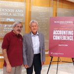 Dr. Steven Balsam standing with Dr. Douglas Carmichael near conference sign