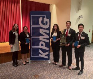 Students with awards and KPMG banner at the competition